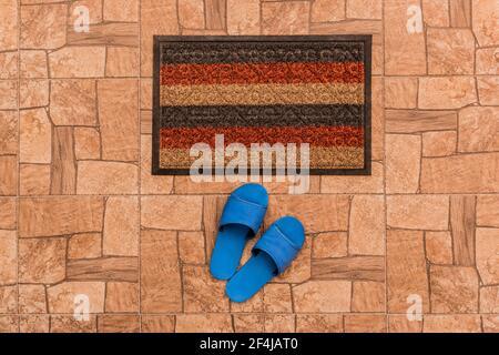 Männer blaue Hausschuhen stehen in der Nähe Fußmatte auf einem braunen gefliesten Boden Textur Hintergrund, Draufsicht.