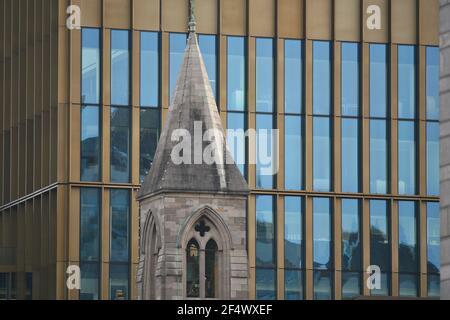 Ein alter Glockenturm aus Stein mit einer modernen Glasfassade im Hintergrund in Dublin, Irland.