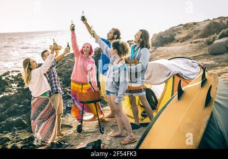 Hipster-Freunde haben gemeinsam Spaß auf Strand-Camping-Party - Freundschaftsreisekonzept mit jungen Leuten Reisende toasten und trinken Bier in Flaschen - Stockfoto