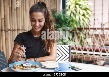 Essen und tropisches Urlaubskonzept. Schöne gebräunte Frau, die im Hotelcafe isst, draußen auf der Terrasse sitzt und das balinesische Frühstück probiert, morgens trinkt
