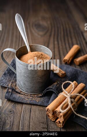 Gesunde Lebensmittel Würze mit medizinischen Eigenschaften, echte Ceylon Zimt Sticks und Pulver in einem Glas auf Holz Hintergrund