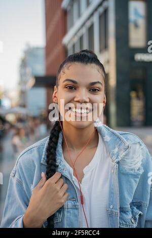 Happy Hipster Frau mit stilvollen Frisur hören Musik im Freien Stockfoto
