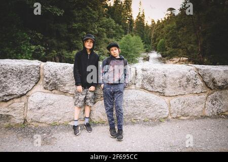 Zwei Freunde posieren für Foto auf der Steinbrücke über Merced Fluss