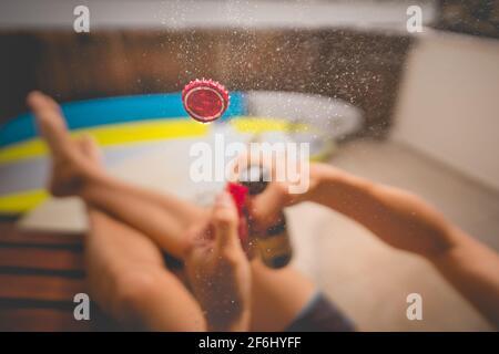 Kaltes Bier trinken und sonnigen Sommertag genießen. Flasche Bier mit Spritzer öffnen. Konzentrieren Sie sich auf die Kappe in der Luft.
