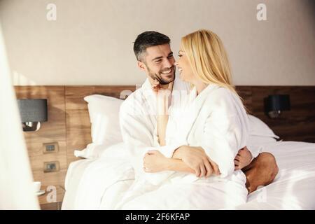 Flitterwochen, frisch verheiratete Paare küssen und Zärtlichkeit in der Wärme eines bequemen Bettes mit weißen Laken. Sie sitzt auf seinem Schoß und er umarmt sie. Gi