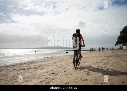 Ein Mann, der auf dem Milford-Strand mit Rangitoto Island in der Ferne radelt. Unscharf Menschen und Hunde gehen am Strand.