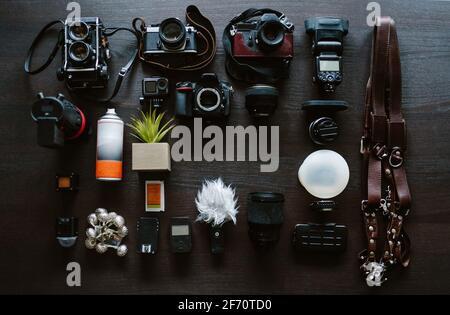 Draufsicht auf den Hochzeitsfotografen im Arbeitsbereich. Set von digitalen und analogen Kameras, Blitz, Kamerazubehör auf dunklem Hintergrund. Arbeitskonzept. Stockfoto