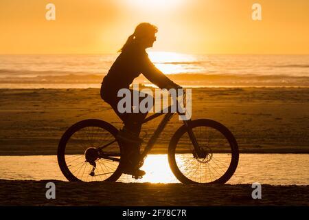 Eine Frau fährt am Strand mit dem Fahrrad Oregon Küste gegen eine orange untergehende Sonne als Teil Eines gesunden Lebensstils Stockfoto