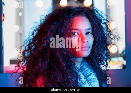 Cute attraktive schwarze Frau Rahmen durch glühende Lichter mit dicken Lockiges Haar, das die Kamera mit einem seitlichen Blick beobachtet Beleuchtet von einem farbenfrohen rosafarbenen Studio Stockfoto