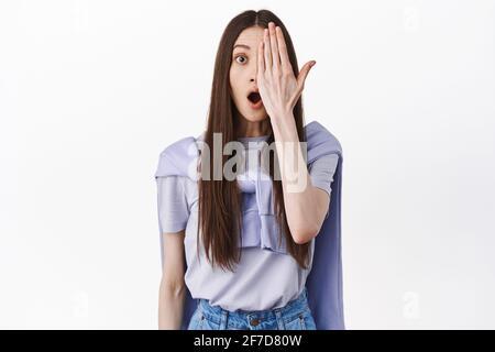 Das Mädchen sieht überrascht aus, wenn die halbe Gesichtshälfte eine geschlossene Handfläche hat, staunt über die Kamera, schaut sich etwas Cooles an und steht auf weißem Hintergrund