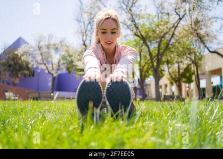 Junge Frau, die sich vor dem Laufen im Park dehnt
