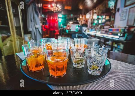 Aperitif-Drinks und Shots warten auf einem Servierbrett in einer Bar, die auf die ersten Gäste bei einer Parade wartet. Partyatmosphäre und ein paar Drinks im Vordergrund