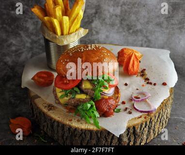 Burger auf Vollkornbrötchen mit Salat und gegrillter Kartoffel auf Holzplatte. Nahaufnahme