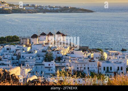 Wunderschöne Aussicht auf die berühmten traditionellen weißen Windmühlen bei Sonnenuntergang, Mykonos, Griechenland. Weiß getünchte Häuser, verschwommener Sommerabend, mediterraner Lebensstil