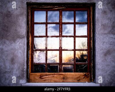 Altes Fenster mit der Spiegelung des Himmels auf einem Sonnenuntergang im Sommer
