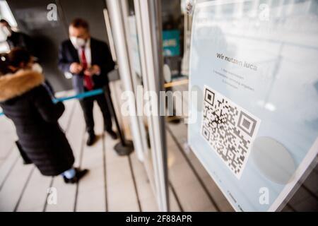Berlin, Deutschland. April 2021. Ein QR-Code zum Herunterladen der Luca App hängt am Eingang eines Bekleidungshauses am Alexanderplatz. Die App dient zur Bereitstellung von Daten für eine mögliche Kontaktverfolgung. Quelle: Christoph Soeder/dpa/Alamy Live News
