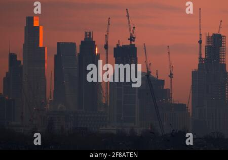 London, Großbritannien. 13. April 2021. Die Morgenröte bricht über den Wolkenkratzern im Zentrum Londons an, und das Sonnenlicht reflektiert die oberen Stockwerke von 22 Bishopsgate, dem 62-stöckigen, 912 Fuß hohen Bürogebäude in der City of London. Quelle: Malcolm Park/Alamy Live News. Stockfoto