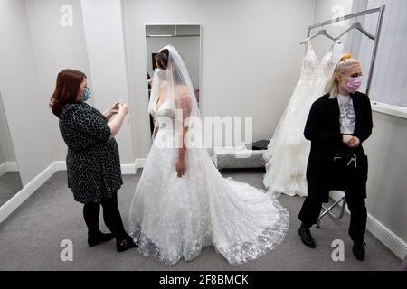 Die zukünftige Braut Erin Barwell versucht sich zum ersten Mal an Kleidern, seit diese Woche nicht unbedingt notwendige Einzelhändler wiedereröffnet wurden. Erin, aus Stoke-on-Trent, wird nächsten Februar heiraten und sich nach der weiteren Lockerung der Sperrbeschränkungen in England bei Roberta's Bridal in Burslem, Stoke-on-Trent, Kleider anprobiert. Bilddatum: Dienstag, 13. April 2021. Stockfoto
