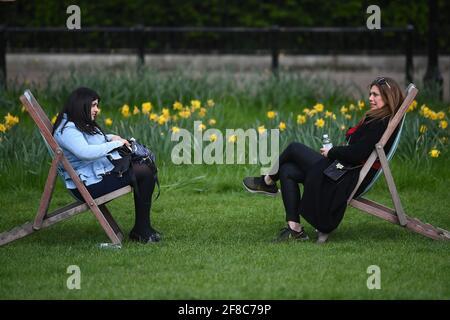 Zwei Frauen sitzen in Liegestühlen im Green Park, London. Bilddatum: Dienstag, 13. April 2021. Stockfoto