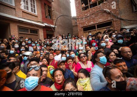 Bhaktapur, Nepal. April 2021. Die Menschen beobachten, wie eifrige Anhänger das Sindoor Jatra Vermillion Powder Festival feiern. Feiernden trugen Wagen der Hindu-Götter und -Göttinnen und schleuderten im Rahmen der Feierlichkeiten zum nepalesischen Neujahrsfest Millionen Pulver aufeinander. Kredit: SOPA Images Limited/Alamy Live Nachrichten Stockfoto