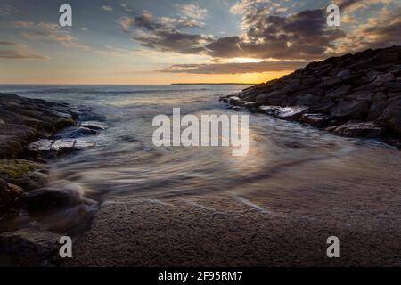 Sonnenuntergang am Aberavon-Strand bei ankommender Flut in Port Talbot, South Wales, Großbritannien