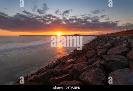 Sonnenuntergang am Aberavon Beach bei ankommender Flut mit Swansea am Horizont, South Wales, Großbritannien