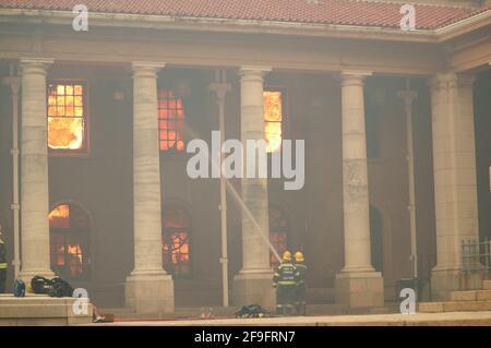 Feuerwehrleute kämpfen gegen Flammen, da die Bibliothek an der Universität von Kapstadt brennt, nachdem am 18. April 2021 ein Buschfeuer an den Hängen des Tafelbergs in Kapstadt, Südafrika, ausbrach. REUTERS/Mike Hutchings