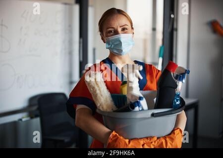 Reinigungskraft in einer Gesichtsmaske, die ihre Reinigungsprodukte zeigt