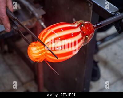 Hände Formen geschmolzenes Glas mit langem Messerheber. Kunst und Handwerk Arbeiter Gießen Glas während Blaskunst Stück i Fabrik. Traditionelles tschechisches Glas Stockfoto