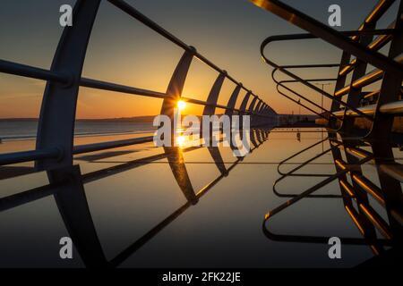 Sonnenuntergänge auf einem Metallsitz an der Aberavon-Promenade in Port Talbot, South Wales, Großbritannien