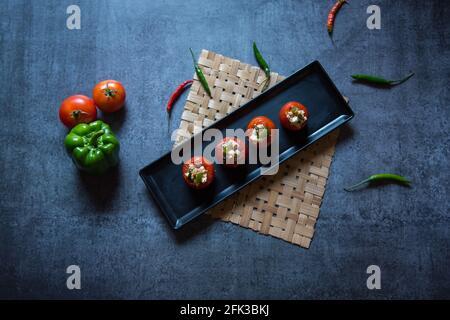 Gefüllte Tomaten, eine indische Vorspeise, die in Weißöl mit Käse und Gemüse zubereitet wird. Draufsicht.