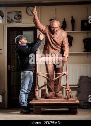 Andrian Melka verleiht seiner zwei Meter hohen Tonstatue von Captain Sir Tom Moore in seinem Atelier in der Nähe von York den letzten Schliff. Der Bildhauer ist Crowdfunding, um die Arbeit in Bronze gießen zu lassen, damit er sie dem Leeds Teaching Hospitals NHS Trust spenden kann. Bilddatum: Mittwoch, 28. April 2021.