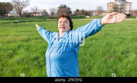 Glückliche ältere Frau in Sportkleidung, die im Park Sport macht, mit ihren Armen an den Seiten ausgebreitet. Internationaler Tag der Älteren. Die Konz