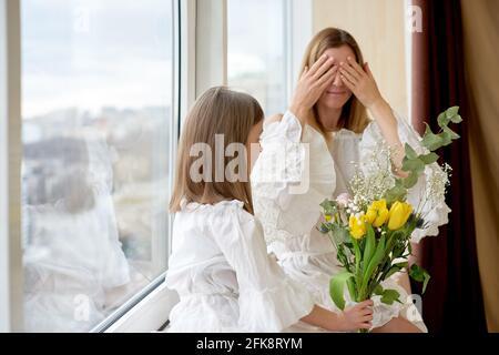 Familienurlaub und Zweisamkeit zu Hause. Alles gute zum Muttertag! Kind Tochter gratuliert Mutter und gibt ihr Blumen Tulpen