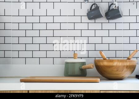 Nahaufnahme-Küche mit Topf, Holz hacken, Holzbadewanne und zwei Keramik-Kaffeetassen auf moderner Theke, Innenausstattung und Wohnkultur in modernem Stil
