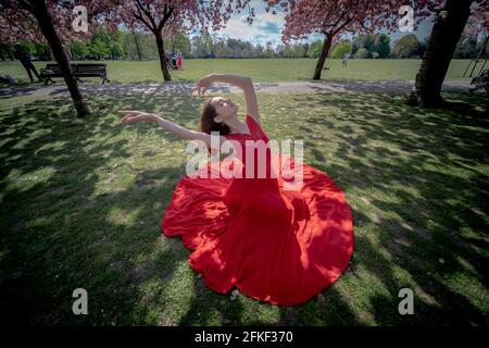 London, Großbritannien. Mai 2021. UK Wetter: Sonnenschein blüht im Greenwich Park. Rebecca Olarescu, eine Meisterschülerin der Screendance an der London Contemporary Dance School (LCDS), genießt die sonnige Sonne an den Feiertagen, indem sie in der Nähe der lebhaften Kirschblütenbäume im Greenwich Park posiert. Kredit: Guy Corbishley/Alamy Live Nachrichten