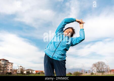 Wellness und Sport. Lächelnde ältere Frau in Sportkleidung, die im Park Sport macht. Neigt sich zur Seite. Ansicht von unten. Internationaler Tag des Älteren P