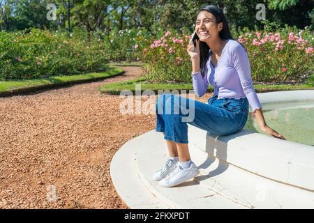 Schöne junge Latina, die am Morgen lächelnd auf dem Rand eines Springbrunnens sitzt und am Handy telefoniert.