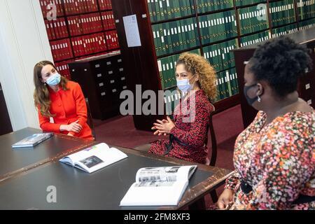 """Die Herzogin von Cambridge spricht mit den """"Hold Still""""-Teilnehmern Naz Maleknia (Mitte) und Claudia Burton (rechts) während eines Besuchs im Archiv der National Portrait Gallery im Zentrum Londons, um die Veröffentlichung des """"Hold Still""""-Buches zu markieren. Bilddatum: Freitag, 7. Mai 2021."""