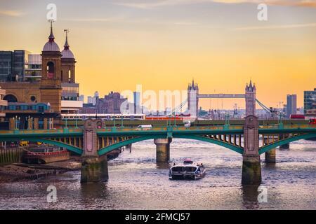Orangefarbener Sonnenuntergang mit dem Stadtbild Londons, einschließlich Cannon Street Railway Bridge, Southwark Bridge und Tower Bridge
