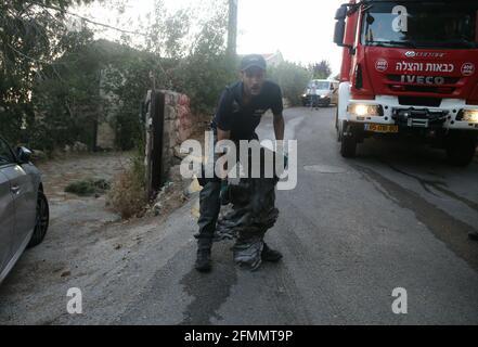 Jerusalem. Mai 2021. Ein israelischer Polizist trägt ein Stück Überreste einer Rakete, die am 10. Mai 2021 in den Außenbezirken Jerusalems aus dem Gazastreifen abgeschossen wurde. Aktivisten im Gazastreifen feuerten am Montag sieben Raketen auf den Raum Jerusalem ab, als die Gewalt zwischen Israelis und Palästinensern sich immer weiter ausnahm. Kredit: Muammar Awad/Xinhua/Alamy Live Nachrichten