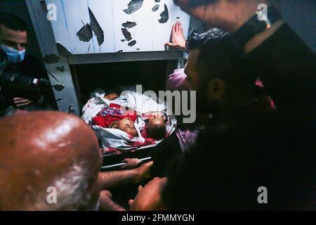 Gaza-Streifen. Jerusalem, 10. Mai 2021 (ANMERKUNG DER REDAKTION: Bild zeigt den Tod) Palästinenser inspizieren die Leichen von Kindern, die bei gewalttätigen Zusammenstößen zwischen Israelis und Palästinensern getötet wurden, an einer KrankenhausLeichenschauhalle im nördlichen Gazastreifen. Am 10. Mai wurden in Jerusalem Sirenen geblasen, nachdem Raketen aus dem Gazastreifen abgefeuert wurden. Nach Angaben der IDF wurde ein israelischer Bürger in einem nahegelegenen Auto leicht verletzt und zur Behandlung evakuiert. Das Gesundheitsministerium in Gaza gab kurz nach der Tötung von etwa zwanzig Menschen nach einem israelischen Angriff auf den nördlichen Teil des Gazastreifens bekannt.