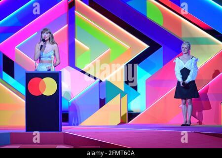 Taylor Swift nimmt den Global Icon Award entgegen, wie Maisie Williams während der Brit Awards 2021 in der O2 Arena in London sieht. Bilddatum: Dienstag, 11. Mai 2021.