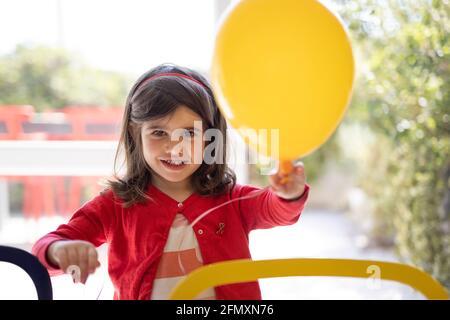 Porträt eines vierjährigen Mädchens, das einen Ballon in der Hand hält. Kleines Mädchen mit Spaß mit einem Ballon.