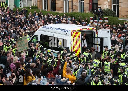 Einer von zwei Männern wird aus dem Rücken eines von Demonstranten umgebenen Einreisewagens in der Kenmure Street, Glasgow, entlassen. Bilddatum: Donnerstag, 13. Mai 2021.
