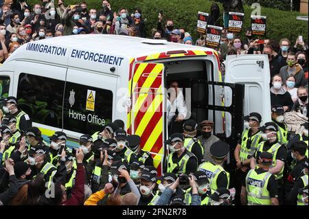 Einer von zwei Männern wird in Begleitung von Mohammad Asif, dem Direktor der Afghan Human Rights Foundation, in der Kenmure Street, Glasgow, von Demonstranten umgeben, von der Rückseite eines Van für Einwanderungsbehörden entlassen. Bilddatum: Donnerstag, 13. Mai 2021.