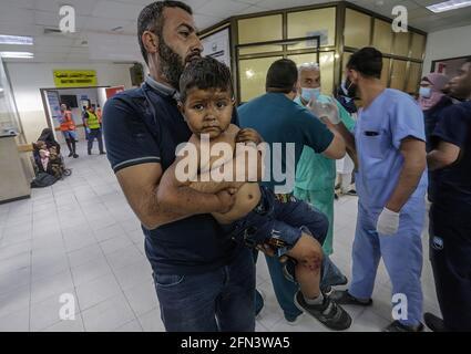 Gaza, Palästina. Mai 13 2021: (HINWEIS DER REDAKTION: Bild enthält grafischen Inhalt.) Ein ververletztes palästinensisches Kind wird nach einem israelischen Luftangriff in Gaza-Stadt in das Al-Shifa-Krankenhaus gebracht, um behandelt zu werden. Als Reaktion auf tagelang gewalttätige Auseinandersetzungen zwischen israelischen Sicherheitskräften und Palästinensern in Jerusalem starteten verschiedene palästinensische Gruppen von Aktivisten in Gaza seit dem 10. Mai Raketenangriffe, bei denen bis heute mindestens sieben Israeliten getötet wurden. Quelle: SIPA US/Alamy Live News