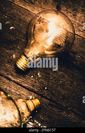 Stillleben konzeptuelle Objekte auf einer freistehenden glühenden Glühbirne, die magisch auf alten Grunge-Holzboden leuchtet. Erhellende Inspiration