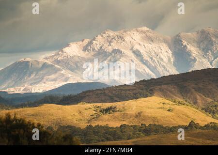 Retro-getönte ländliche Szene auf hügeligen, grasbewachsenen Hügeln vor steinigen Berggipfeln. West Coast Range, West Coast Tasmania, Australien