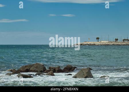 seascape mit Felsen im Vordergrund und Wellenbrecher im Hintergrund